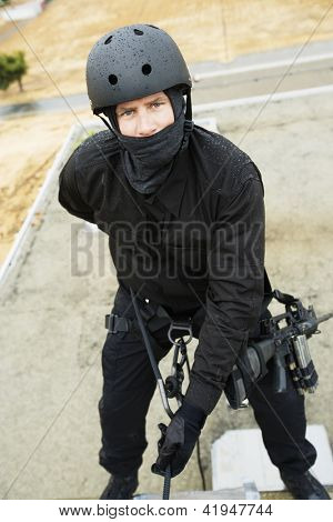 Portrait of commando rappelling down outside building