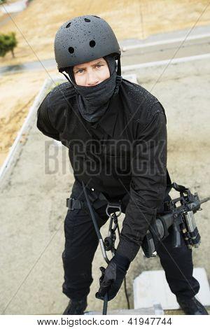Portrait of commando rappelling down outside building