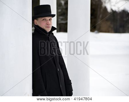 Man In Hat Relies On White Column