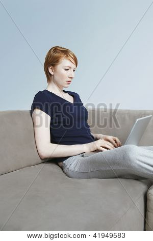 Young woman relaxing on sofa while using laptop at home