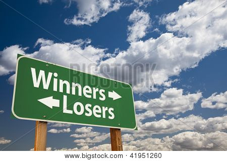 Winners, Losers Green Road Sign Over Dramatic Clouds and Sky.