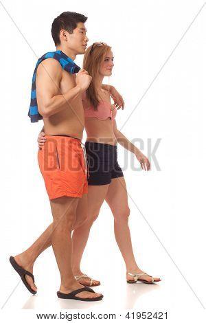 Young couple in swimwear. Studio shot over white.