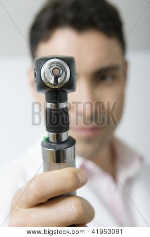 Portrait of male doctor holding otoscope in clinic