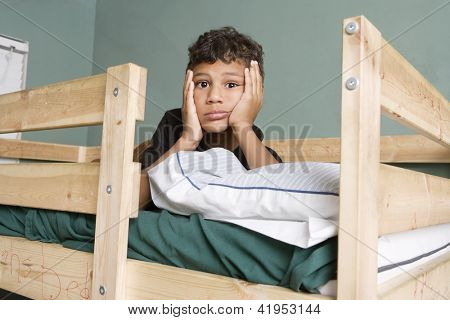 Tired little boy lying on bunk bed