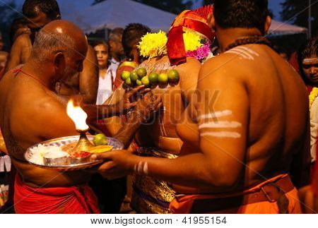 KUALA LUMPUR - JANUARY 27: A Hindu priest pierces the back of a devotee with skin hooks before his walk to the Batu Caves temple in Malaysia on January 27, 2013 during the Thaipusam festival.