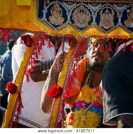 KUALA LUMPUR - JANUARY 27:A devotee with a his tongue skewered carry a kavadi as an act of devotion to Lord Muruga walks to the Batu Caves temple in Malaysia on Jan 27, 2013 at the Thaipusam festival.