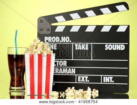 Movie clapperboard, cola and popcorn on background