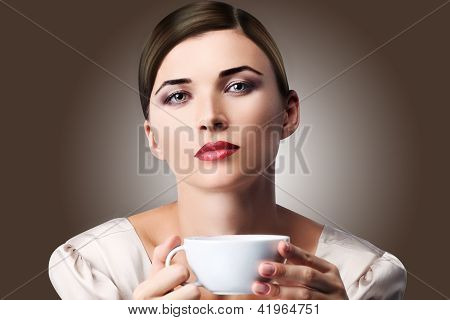 Beautiful happy young woman with cup of aromatic coffee or tea in hands on natural background