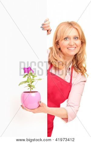 A smiling agricultural woman holding a flower pot and posing behind a blank panel isolated against white background