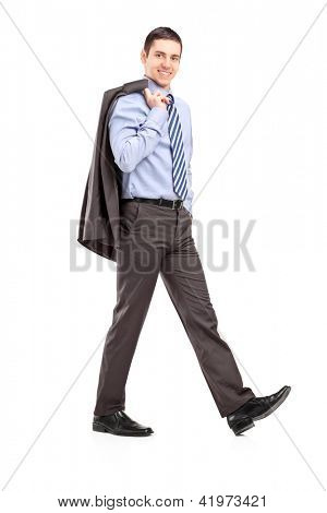 Full length portrait of a young businessman walking with a coat over shoulder isolated on white background