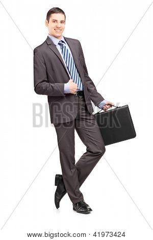 Full length portrait of a smiling businessman holding a leather briefcase and leaning against wall isolated on white