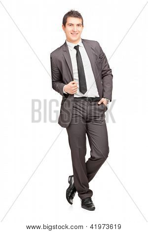 Full length portrait of a smiling male businessman leaning against wall isolated on white background