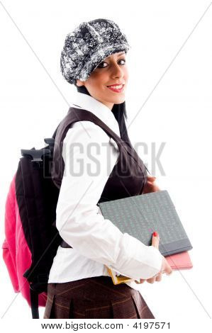 Female Student In Cap With Her School Bag And Study Material