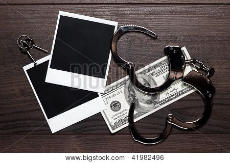 handcuffs money and old photos detective concept