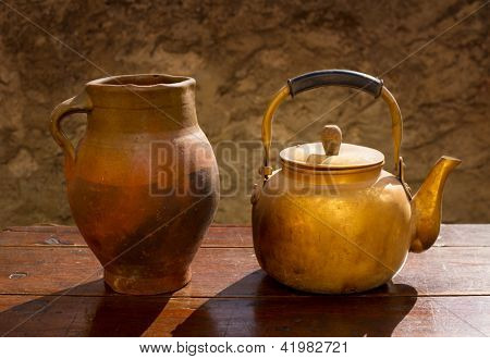 Antique brass teapot on vintage wooden table and clay jar