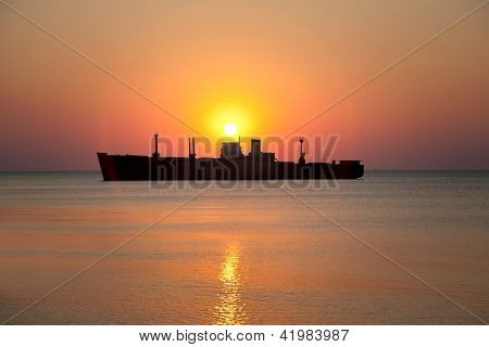 Lonely military ship against  marine sunset