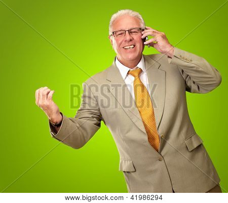 Senior Business Man Talking On Phone Isolated On Green Background