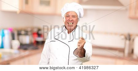 Portrait Of A Senior Male Chef Holding A Beater, Indoor
