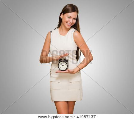 Happy Woman Holding Clock against a grey background