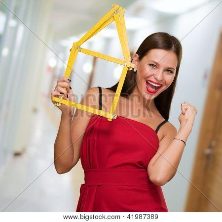 Frau Holding Haus Frame tun eine Erfolg-Geste in einer Passage Weg