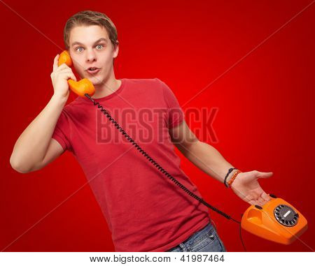 Portrait of a young man talking on vintage phone on red background