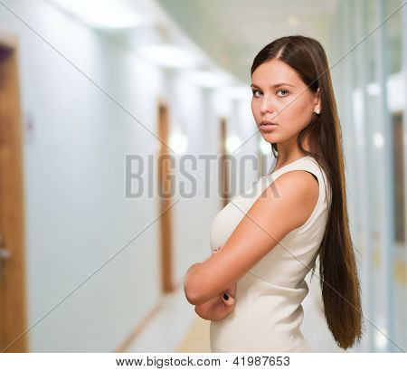 Young woman with her arms crossed in a passage way