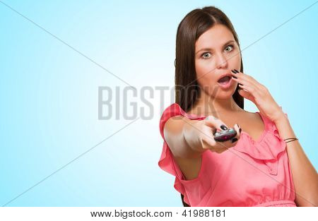 Portrait Of A Young Woman Holding Remote Control against a blue background