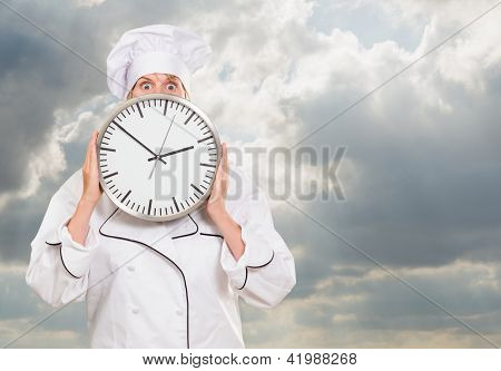 worried chef hiding behind a clock against a cloudy sky background