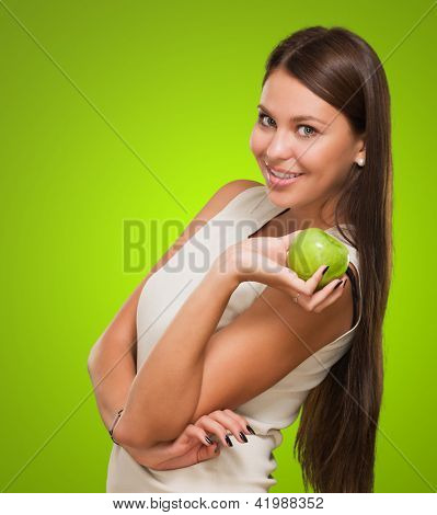 Portrait Of A Young Woman Holding Green Apple against a green background