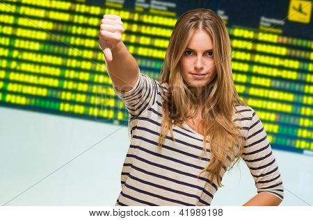 Young Woman Showing Thumb Down Sign at an airport