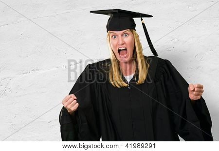 Portrait of an angry graduate against a concrete wall background