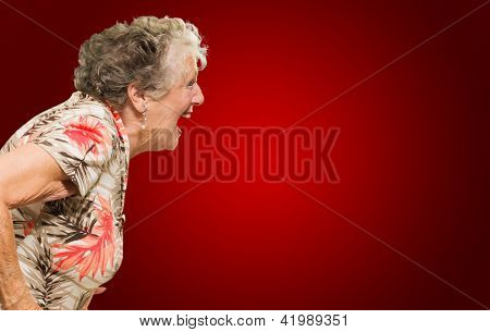 Portrait Of Shocked Senior Woman On Red Background