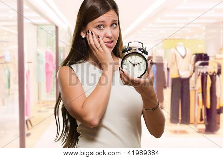 Worried Woman Holding Alarm Clock at a clothes shop