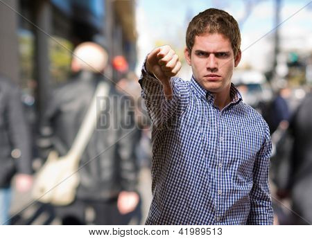 Young Man Showing His Thumb Down  against a street background