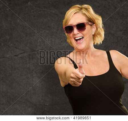 Mature Woman Showing Thumbs Up Sign On Wall