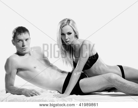 Black and white portrait of young sexy couple over white background