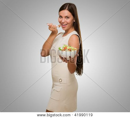 Portrait Of A Young Woman Eating A Salad against a grey background
