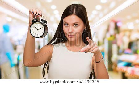 Jovem mulher segurando relógio e apontando para um shopping