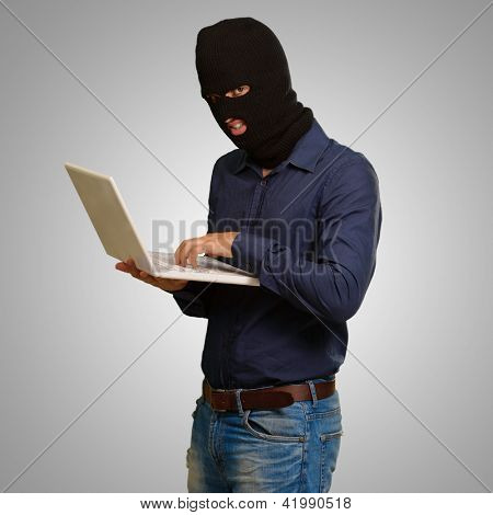 young male thief holding laptop isolated on grey background