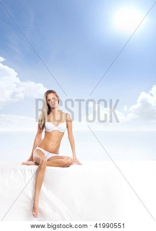 Young, healthy and attractive woman over the sea and sky background
