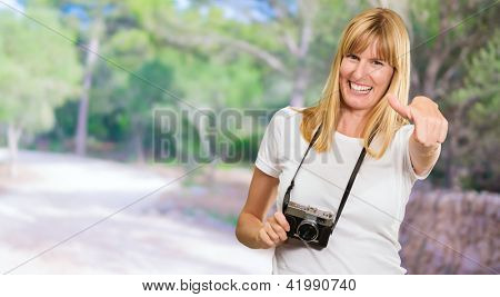 Happy Woman With Old Camera Showing Thumb Up against a forest background