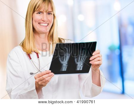 Portrait Of Happy Doctor Holding X-ray against an abstract background