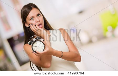 Portrait Of A Shocked Woman Holding a Clock against an abstract background