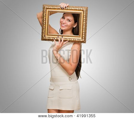 Portrait Of A Young Woman Holding Frame against a grey background
