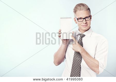 Friendly young businessman pointing finger at empty notepad with space for text, isolated.