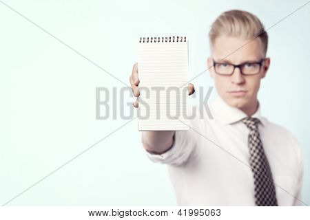 Serious young businessman showing empty notepad with space for text, isolated.