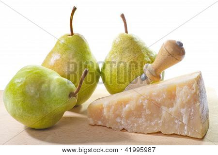 piece of parmesan cheese with pear on cutting board