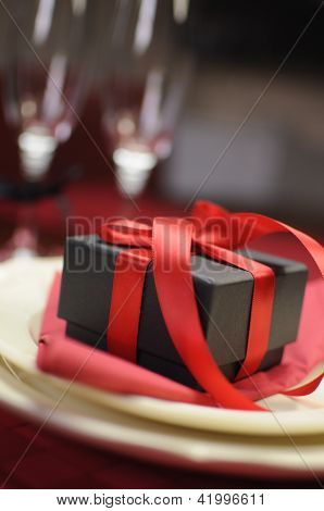 Black Box Present Gift With Red Ribbon On Romantic Valentine Table Setting.
