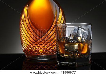 Closeup of an elegant decanter and a glass of scotch on the rocks. Horizontal format on a light to dark gray background.