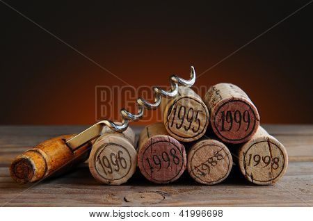 Closeup of a group of wine corks and a corkscrew on a rustic wood table and a light to dark warm background.